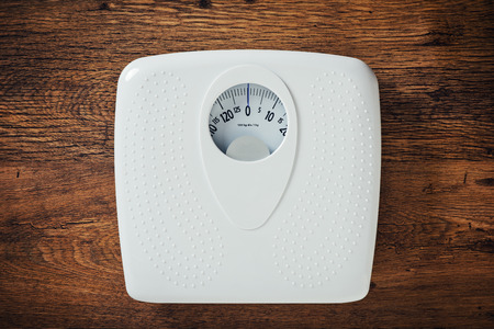 scale weight: White scale on a wooden table top view, fitness and weight loss concept