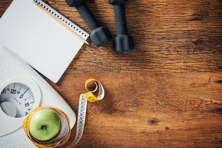 the wellbeing: Fitness and weight loss concept, dumbbells, white scale, tape measure and notebook on a wooden table, top view Stock Photo