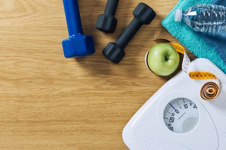 equipos: Fitness y pérdida de peso concepto, pesas, cinta métrica, toallas blancas escala y la botella de agua sobre una mesa de madera, vista desde arriba