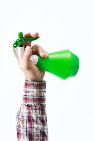 garden tool: Gardeners hand holding a green sprayer bottle on white background