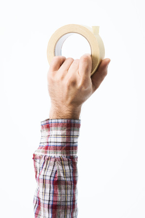 sticky hands: Male hand holding a roll of masking tape on white background