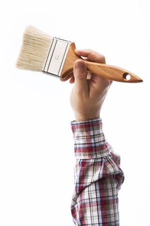brocha de pintura: Decorators male hand holding a paint brush on white background, diy and home renovation concept Foto de archivo