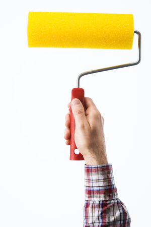 painter and decorator: Decorators male hand holding a painting roller on white background, hobby and home renovation concept Stock Photo