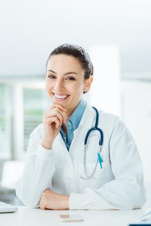 ヘルスケア: 自信を持って女性医師事務所の机に座って、あご、健康管理と予防概念で手のカメラで笑顔