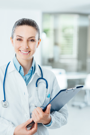 medical professional: Smiling female doctor with lab coat in her office holding a clipboard with medical records, she is looking at camera Stock Photo