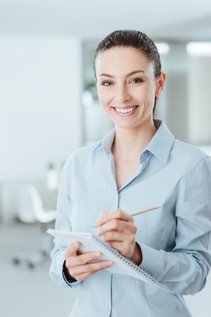 secretarias: Secretaria profesional joven escribiendo notas en un bloc de notas y sonriendo a la cámara, ella está de pie en la oficina Foto de archivo