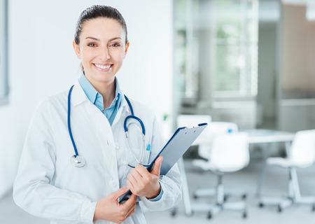 Lächelnder weiblicher Doktor mit Laborkittel in ihrem Büro mit einem Klemmbrett mit medizinischen Aufzeichnungen, sie ist auf der Suche Kamera Lizenzfreie Bilder