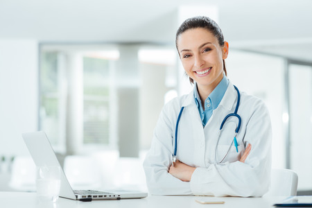 doctor care: Confident female doctor sitting at office desk and smiling at camera, health care and prevention concept