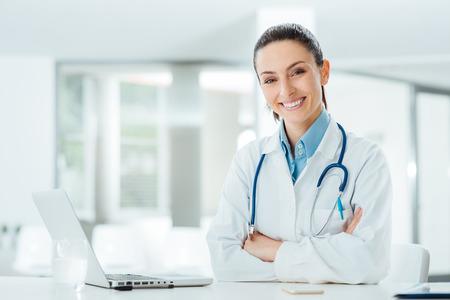 doctores: Doctor de sexo femenino confidente que se sienta en el escritorio de oficina y sonriendo a la c�mara, la atenci�n de la salud y el concepto de la prevenci�n