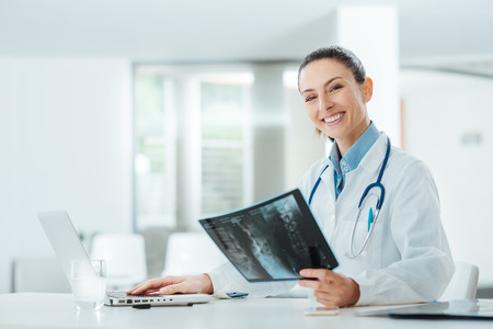 office uniform: Smiling confident female doctor sitting at office desk and examining a patients x-ray, she is looking at camera Stock Photo