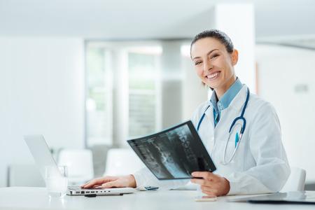 lekarz: Uśmiecha się pewność kobieta lekarz siedzi na biurko i bada pacjenta x-ray, jest ona patrząc na kamery