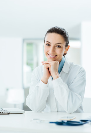 Beautiful female doctor posing and smiling at camera, health care and prevention concept