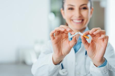 fumar: Mujer sonriente m�dico rompiendo un cigarrillo, dejar de fumar y la prevenci�n concepto
