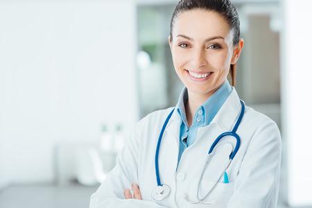 consulta m�dica: Doctor de sexo femenino confidente que presenta en su oficina y sonriendo a la c�mara, la atenci�n de salud y el concepto de prevenci�n