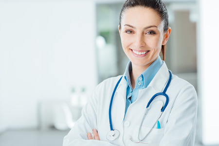 Confident female doctor posing in her office and smiling at camera, health care and prevention concept Stockfoto