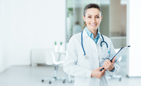office uniform: Smiling female doctor with lab coat in her office holding a clipboard with medical records, she is looking at camera Stock Photo
