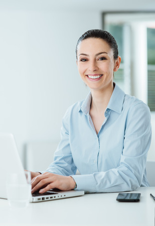 social networking: Smiling young businesswoman working at office desk and typing on a laptop, she is looking at camera