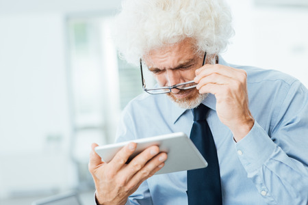 Businessman having eyesight problems, he is using a tablet and adjusting his glasses, office interior on background