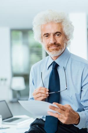 hombre pensando: Confiado sonriendo madura papeleo empresario lectura y la celebración de gafas, él está mirando a la cámara