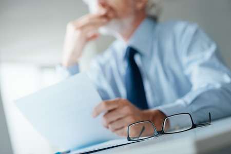 Pensive businessman with hand on chin looking away and holding a document, selective focus, glasses on foreground 스톡 콘텐츠