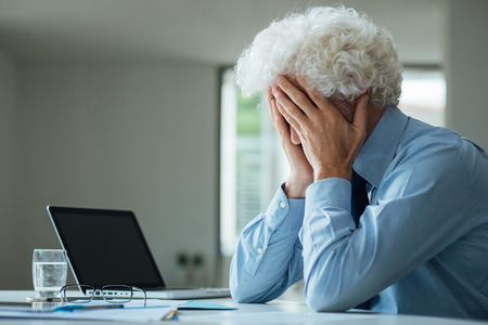 work stress: Exhausted businessman with head in hands sitting at office desk, failure and depression concept