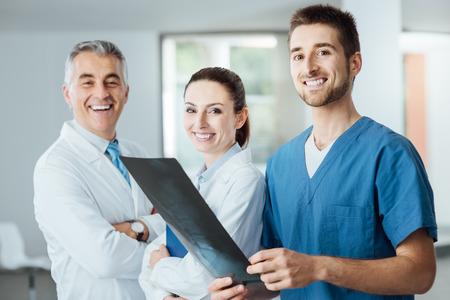 cirujano: Equipo m�dico compuesto por m�dicos y cirujano sonriendo a la c�mara y examinar la imagen de rayos x de un paciente de la columna vertebral humana, el trabajo en equipo y el concepto de la asistencia