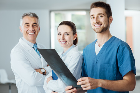 Medical team composed of doctors and surgeon smiling at camera and examining a patient's x-ray image of human spine, teamwork and assistance concept