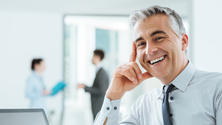 Confident handsome businessman sitting at office desk and smiling at camera, office interior and business people standing on background, selective focus