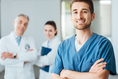 Young doctor posing and smiling at camera and professional medical staff on background, selective focus