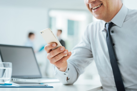 Businessman sitting at office desk using a touch screen smart phone, hands close up, office interior and business people on background, selective focus Stock Photo