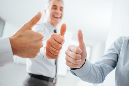 Hombres de negocios alegres pulgares para arriba, las manos se cierran para arriba, éxito, logro y concepto de satisfacción Foto de archivo