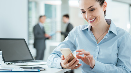 Confident smiling business woman sitting at office desk and using a smart phone, business people standing on background, selective focus