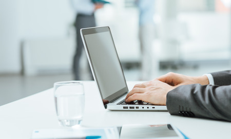 Businessman working at office desk and typing on a laptop, selective focus, hands close up Stock Photo