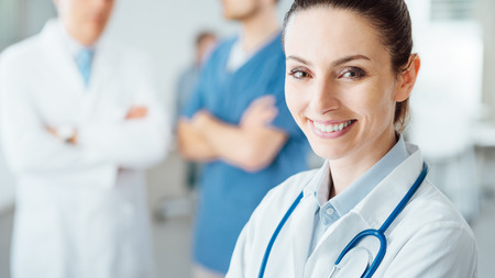 Professional female doctor smiling at camera and posing, medical staff working on background, selective focus Archivio Fotografico