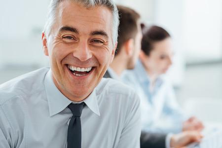 Zelfverzekerd professionele zakenman glimlachen op de camera, kantoor en business team dat werkt op de achtergrond, selectieve aandacht Stockfoto