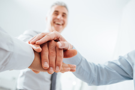 teamwork business: Cheerful business team stacking hands and smiling, teamwork and success concept, hands close up