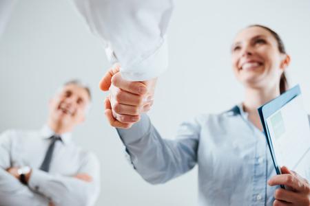 contrato de trabajo: Hombres de negocios confidentes que sacuden las manos y la mujer sonriendo, el reclutamiento y el acuerdo concepto