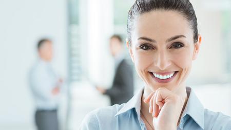 lideres: Confiado bella mujer de negocios sonriente en la oficina posando con la mano en la barbilla y mirando a cámara, interior de oficina y equipo de negocios en el fondo, el enfoque selectivo