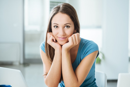 Smiling adolescent girl sitting at desk and posing, she is looking at camera