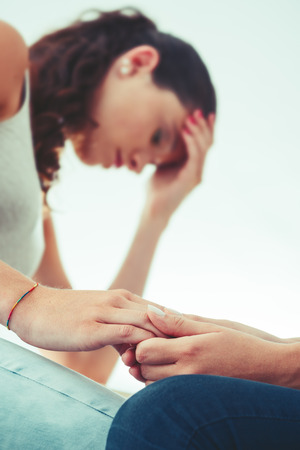 depresión: Muchacha que conforta a su amigo triste deprimido y sosteniendo su mano, el apoyo y la amistad concepto