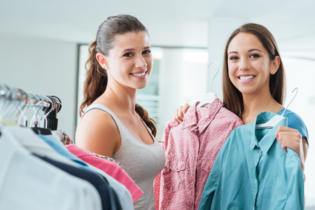 Teenagers shopping women's clothing at the store and smiling at camera, customer satisfaction and quality concept