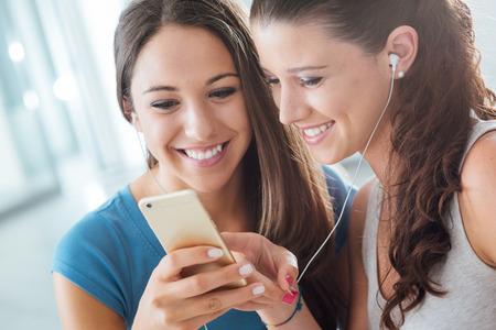 personas escuchando: Chicas jóvenes sonriente bonita que comparten los auriculares y escuchar música con un teléfono inteligente Foto de archivo