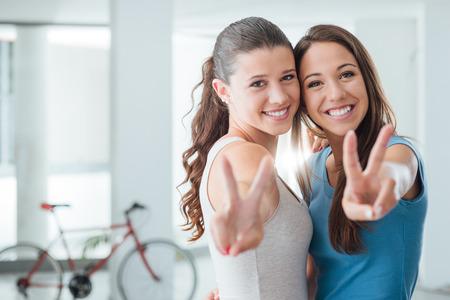 friendship: Mignon adolescentes souriant à la caméra et de faire un concept signe V, l'adolescence et l'amitié