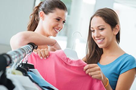 ropa colgada: Muchachas sonrientes bonitas de compras de ropa femenina en la tienda, la moda y el concepto de venta
