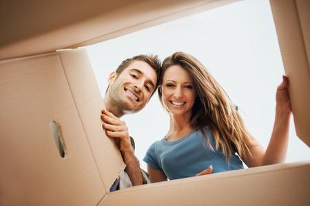 Giovani coppie sorridenti che aprono un contenitore di cartone e che guardano dentro, trasferimento e disimballando concetto Archivio Fotografico - 42511838