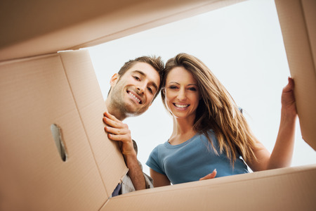 looking at: Smiling young couple opening a carton box and looking inside, relocation and unpacking concept