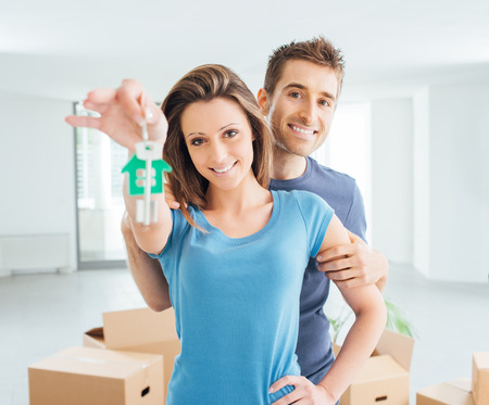 cardboard house: Young smiling couple holding their new house keys, real estate and relocation concept