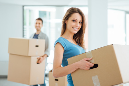 house property: Happy smiling couple moving in a new house and carrying carton boxes, relocation and renovation concept