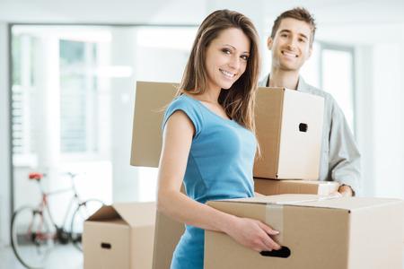 parejas jovenes: Sonriente pareja feliz que se traslada a una nueva casa y llevando cajas de cart�n, reubicaci�n y renovaci�n concepto