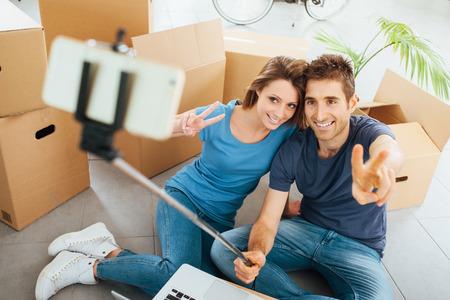bienes raices: Sonriente joven pareja sentada en su nuevo piso de la casa, rodeado de cajas de cart�n y tomando selfies usando un palo selfie